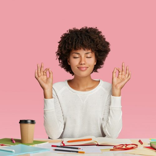People, harmony and work concept. Satisfied dark skinned woman with Afro haircut, meditates at workspace, keeps eyes closed, wears white sweater, sits at desktop, writes information in notepad
