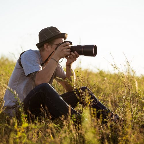 Young male photographer in hat taking picture, sitting in field. Outdoor background.